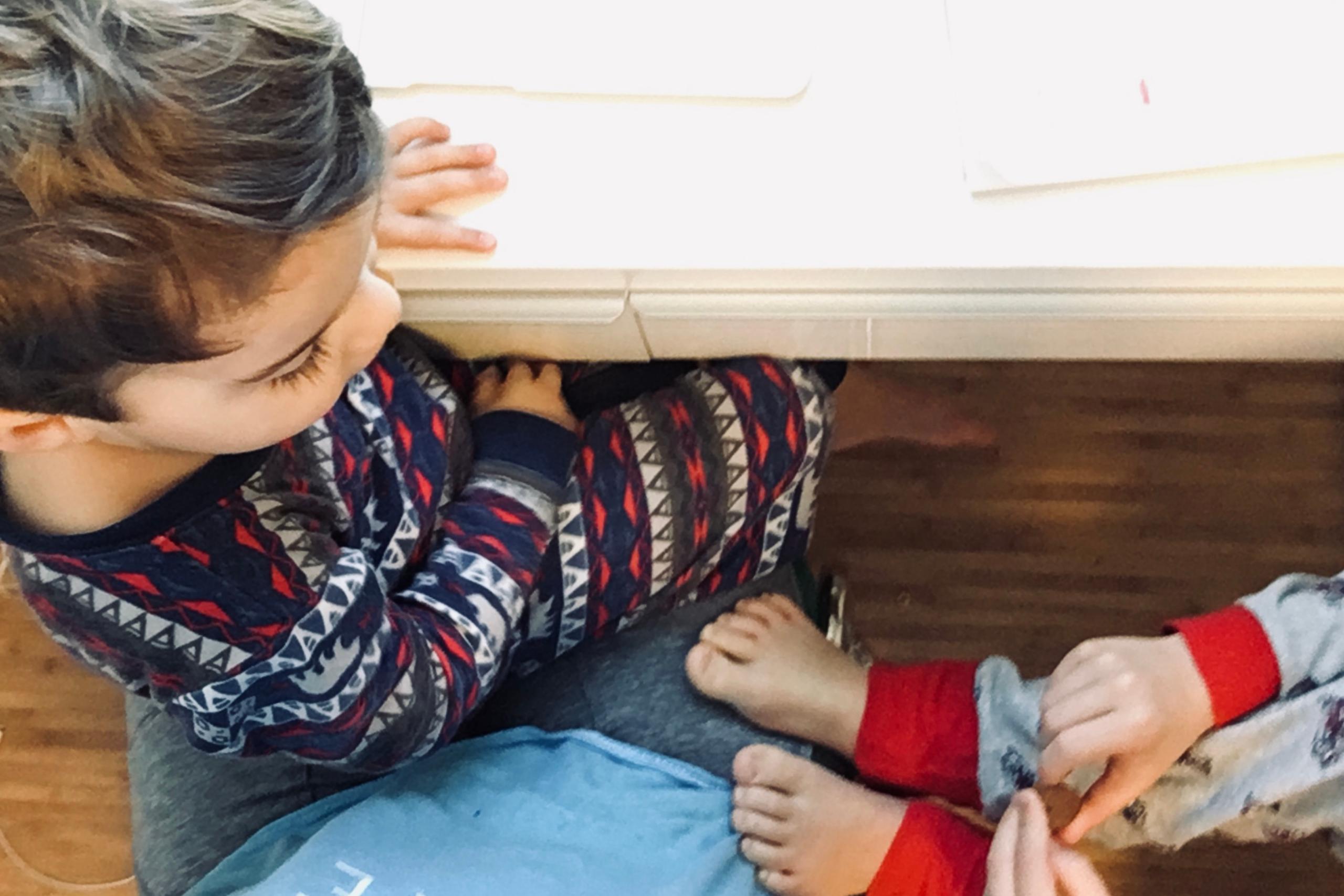 un mère tente de travailler avec ses enfants sur les genoux